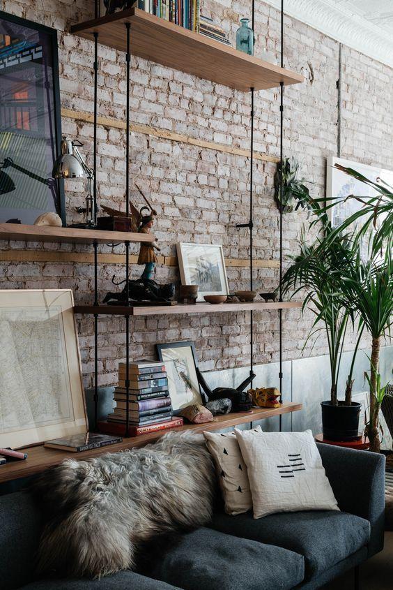 Một giá sách DIY rất tương ứng với bức tường gạch thô mộc phía sau. Những giá để đồ có phong cách như thế này, sẽ rất hợp với đồ trang trí loại mộc bản, gốm hoặc sách. Chất liệu và độ tương ứng về style sẽ tạo nên sự hài hòa và ấm cúng cho không gian tiếp khách của bạn.