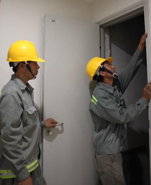 Công nhân Lecmax đang kiểm tra cửa thoát hiểm chống cháy mới lắp đặt tại Tòa nhà Gold View Quận 4, TP.HCM.