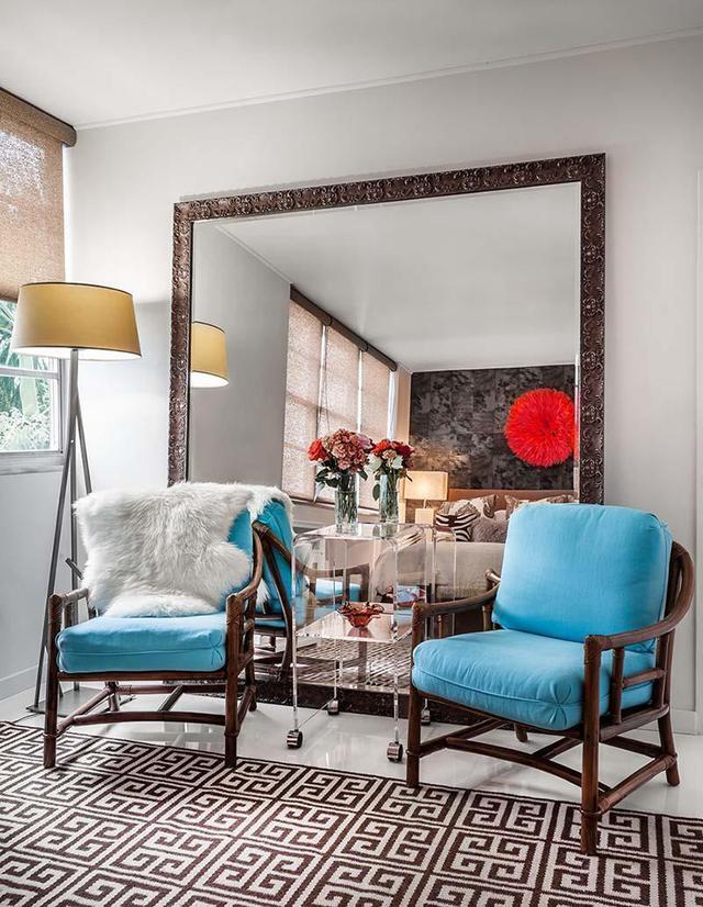 Tấm gương lớn giúp ánh sáng đi sâu hơn vào phòng khách.