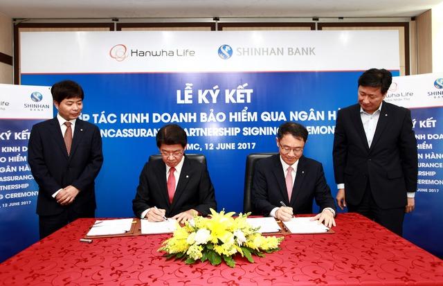 Ông Back Jong Kook, Chủ tịch HĐQT kiêm TGĐ Hanwha Life Việt Nam (trái) và ông Shin Dong Min –TGĐ Ngân hàng Shinhan tại Việt Nam (phải) ký kết thỏa thuận hợp tác.