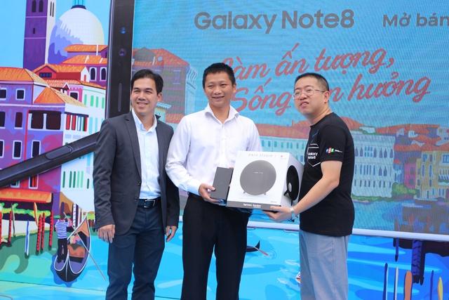 Ông Nguyễn Quang Hiền Huy và ông Nguyễn Việt Anh trao máy và quà cho khách hàng đến nhận máy tại FPT Shop 261 Khánh Hội, quận 4.