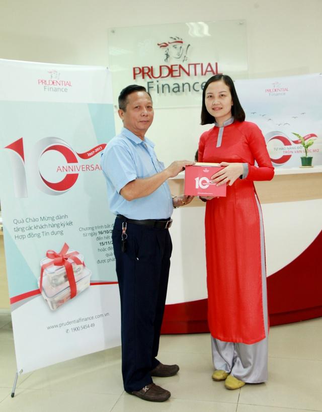 Một khách hàng có khoản vay tín chấp mới vui vẻ đón nhận quà tặng đặc biệt từ Prudential Finance nhân sự kiện kỷ niệm 10 năm thành lập.